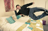 Man levitating above his bed — Stock Photo