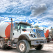 Mixer truck with a beautiful cloudscape in the background - Stock Photo