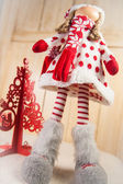 Christmas Doll and a red christmas tree — Stock Photo