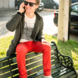 Young man sitting on a bench talking on the phone - Foto Stock