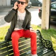 Young man sitting on a bench talking on the phone - Stockfoto