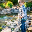 Little blond boy playing in garden — Stock Photo #30398435