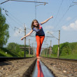 Stock Photo: A beautiful girl walking down the railroad track