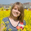 Beautiful girl and yellow rapeseed flowers — Stock Photo