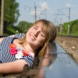 Beautiful girl lying on the rails — Stock Photo