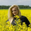 Beautiful girl on rapeseed field — 图库照片