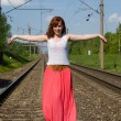 Beautiful girl walks on the rails — Stock Photo