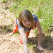 Stock Photo: Girl, crawling through the sand