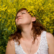 Beautiful girl rest on rapeseed field — Stock Photo