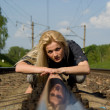 Girl blonde lying on the rails — Stock Photo