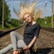 Girl blonde sitting on the rails — Stock Photo