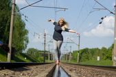 A beautiful girl walking down the railroad track — Stock Photo