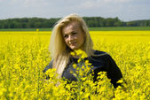 Beautiful girl on rapeseed field — Stock Photo