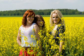 Beautiful girls on rapeseed field — Stock Photo