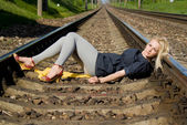 Girl blonde lying on the rails — Stock Photo