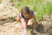 Girl, crawling through the sand — Stock Photo