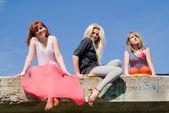 Girls sitting on the bridge — Stock Photo