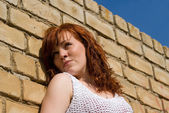 A beautiful red-haired girl standing by the wall — Stock Photo