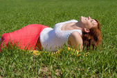 Beautiful girl rests in the meadow — Stock Photo