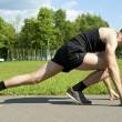 Stock Photo: Guy athlete starts on path in park