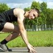 Guy athlete starts on the track — Stock Photo