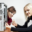 Two girls repairing computer - Stock Photo