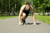 Athlete starts on the path in the park — Stock Photo