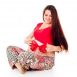 Pregnant girl with a red bow on her stomach — Stock Photo #14026092
