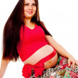 Pregnant girl with a red bow on her stomach — Stock Photo #14026174