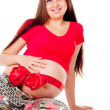 Pregnant girl with a red bow on her stomach — Stock Photo #14026200