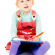 A little girl sits and paints — Stock Photo