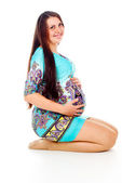 Pregnant girl with a red bow on her stomach — Stock Photo