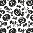 Seamless pattern of pumpkins and skulls — Imagen vectorial