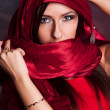 Beautiful girl in the eastern red kerchief - Stock Photo