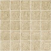 Handwritten alphabet letters on sand — Stock Photo
