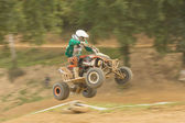 Young rider jumps the quad. Panning shot. — Stock Photo