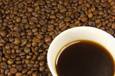 A cup of coffee with a coffe bean — Stock Photo