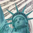 Statue of Liberty and Dollars background — Stock Photo #17980379