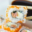 One piece of Maki Sushi in chopsticks — Stock Photo