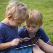 Royalty-Free Stock Photo: The blond boys are playing with the PC tablet outdoor.