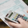 Filling income tax forms with calculator — Stock Photo #20045913