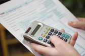 Filling income tax forms with calculator — Stock Photo