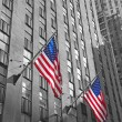 Two American flags with skyscraper background — Stock Photo