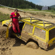 Yellow off road car drowned in muddy terrain — Stock Photo