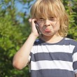 Annoyed blond boy is calling outdoors. — Stock Photo #28739463