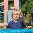 Young blond boy is playing at monkey bars. — Stock Photo