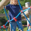Young blond boy is playing at monkey bars. — Stock Photo #32501253