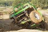 Green off-road car in a difficult terrain — Stock Photo