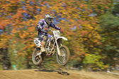 Racer in blue and white is jumping — Stock fotografie