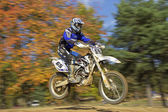 Motocross rider in blue is jumping at race — Foto de Stock